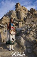 ******** Traditional Hopi girl, Povi Lomayauma 16 year old teenager, dressed in traditionally woven cotton dress holds a woven wicker plaque stands on an ancient staircase leading to the town of Tewa The stone steps are located on the First Mesa near Polacca Arizona