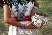 ******** Zuni lady in traditional cotton dress and wearing turquoise squash blossom necklace, bracelets and ring holds a traditional clay pot