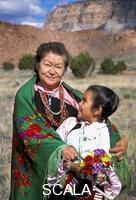 ******** Zuni Grandmother and Granddaughter, Lena Tsethlikia and Cherree Shebala, dressed in traditional clothing stand in a grass field with the landmark Corn Mountain behind them on the Zuni Reservation, New Mexico