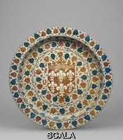 ******** Dish, Manises. 1450 (circa). G.514. Brasero; earthenware; large dish, almost vertical walls, horizontal flange; covered both sides with creamy tin-glaze; painted with yellow-brown lustre and blue on obverse and copper-brown on reverse; obverse, in the centre a crowned coat of arms with a sem of fleurs-de-lis, which probably represent either Ren Valois, Duc d'Anjou, or Angevin quartering; around this, concentric circles with ivy and vine leaves, flowers and fern foliage; two suspension holes; reverse, in lustre a large eagle amongst fern foliage and scrolls.