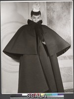 Dahl-Wolfe, Louise (1895-1989) Luki in Balenciaga Coat, Paris. 1953. [model with chin tucked down into cape coat, small pale hat]. Gelatin silver print. Overall, Primary Support: 13 7/8 x 10 13/16 in. (35.3 x 27.4 cm) Image: 13 11/16 x 10 11/16 in. (34.7 x 27.2 cm). Louise Dahl-Wolfe Archive. Inv. N.: 93.72.1